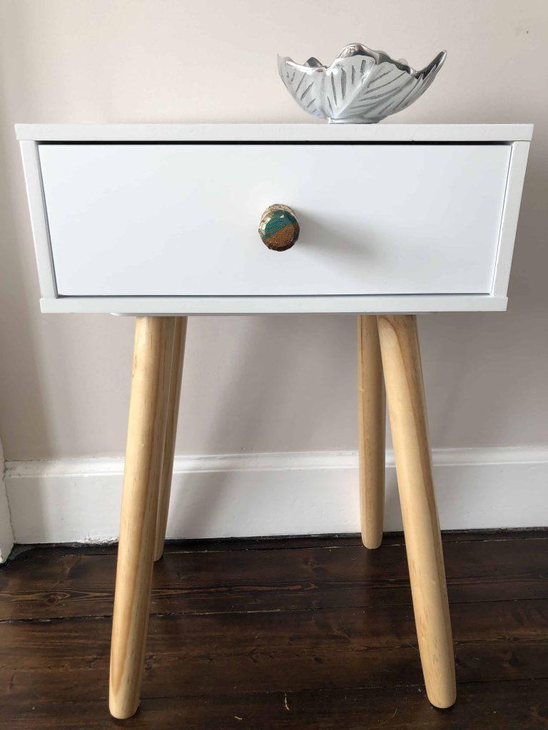 metallic drawer pull on white nightstand